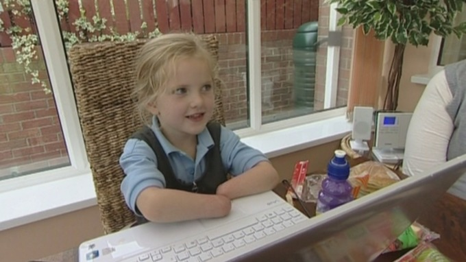 Double-amputee Tilly Lockey sat at laptop as young girl