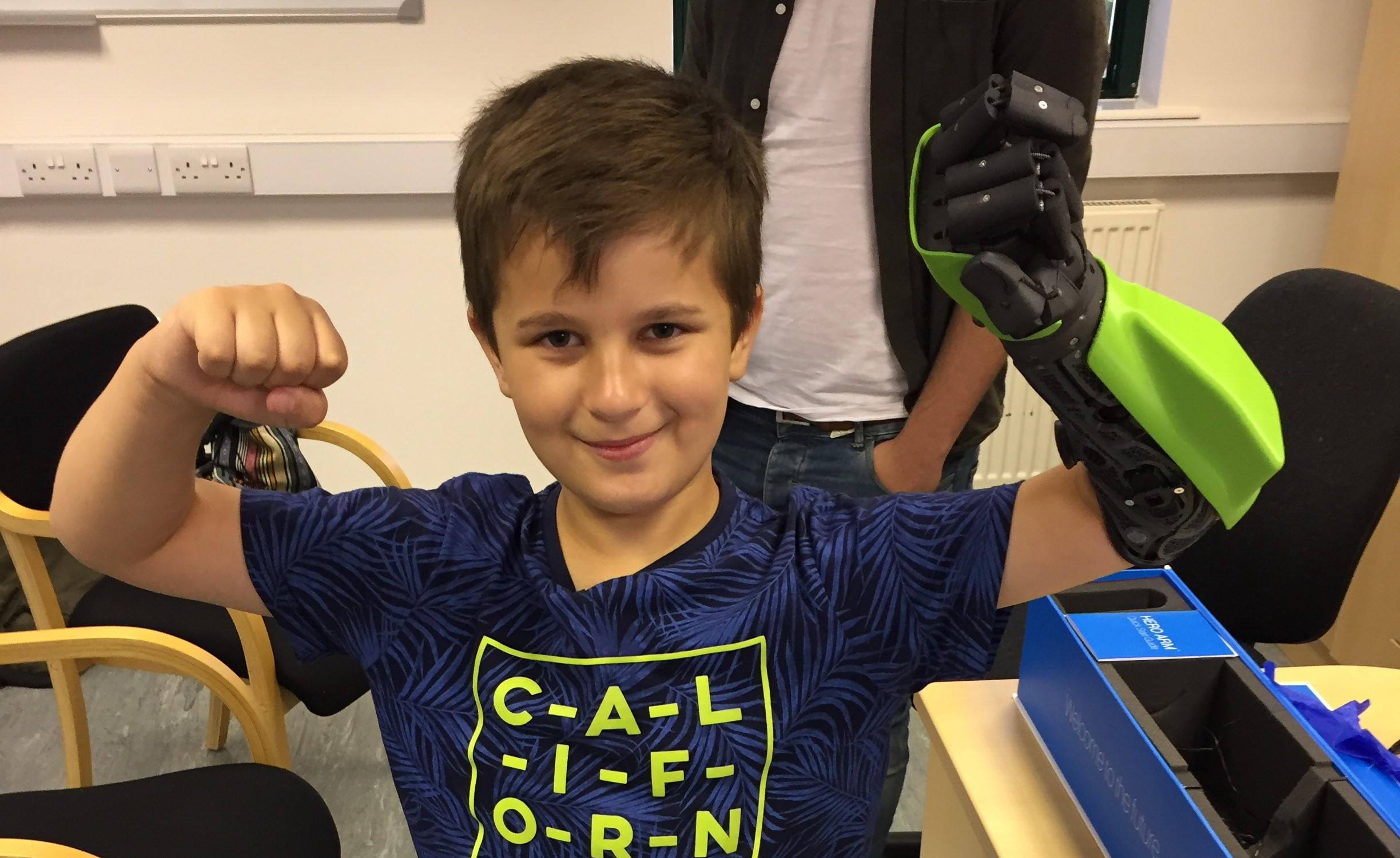 Boy wearing black and green Hero Arm does strong man pose